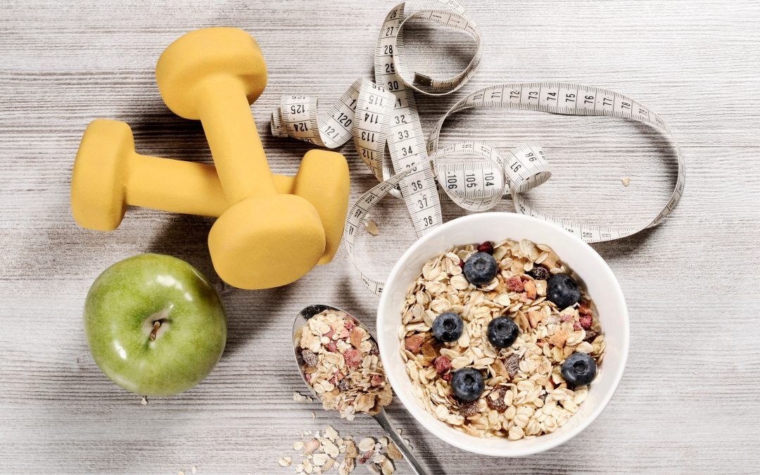 healthy food , healthy lifestyle concept with exercise weights, tape ,fruits and muesli on a wooden background